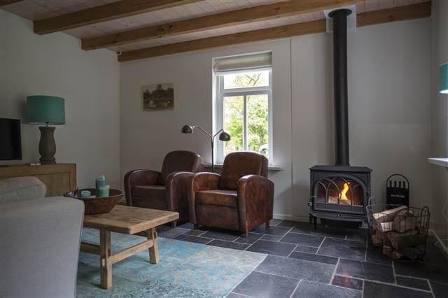 Comfortabele schapenleren fauteuils bij de kachel in vakantiewoning Duins End in Oostvoorne